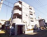 外壁は白いタイル貼り、4階建てのマンションです。