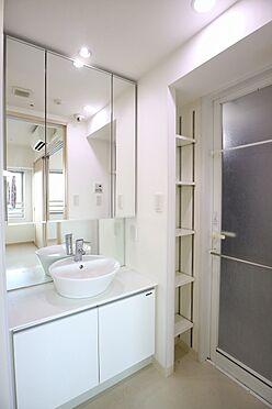 区分マンション-台東区日本堤2丁目 洗面室には、3面鏡付きの独立洗面台に加え、棚が設置されており、タオルなどの収納に便利