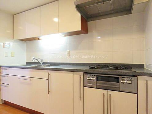 中古マンション-稲城市若葉台2丁目 広々としたシステムキッチンは白を基調とした配色で明るい印象