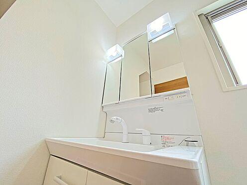 新築一戸建て-日野市西平山2丁目 ハンドシャワー付きの洗面化粧台。収納充実の三面鏡も嬉しいですね