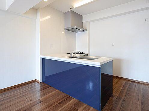 中古マンション-品川区八潮5丁目 暗すぎない無垢の様に見えるブラウンのフローリングに紺に近い青のキッチンが映えます。