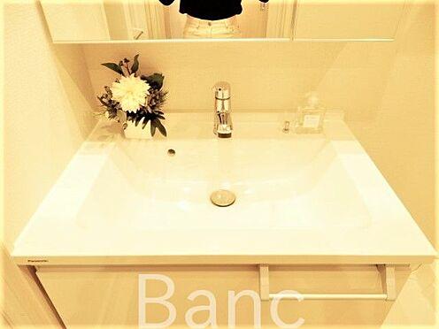 中古マンション-世田谷区経堂5丁目 使い勝手のいい洗面台です。照明、コンセントもついています。鏡面裏は収納になっていて洗面台周りがごちゃごちゃしません。